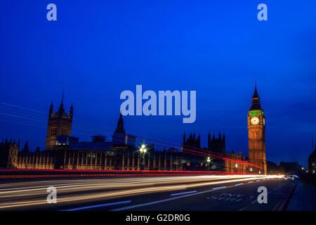 Palacio de Westminster en Londres, y el Big Ben en la noche con el vehículo dejando un rastro a lo largo de la carretera, Foto de stock