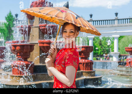 Hermosa muchacha asiática en chino tradicional vestido rojo con paraguas de bambú cerca de Trevi Foto de stock