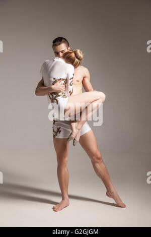 Pareja de gimnasia en trajes blancos posando en el studio Foto de stock