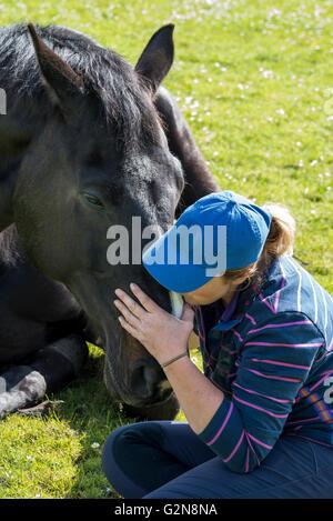 Una mujer y su caballo acostado en un verano en el prado. La mujer muestra afecto a su caballo de Sleepy. Foto de stock