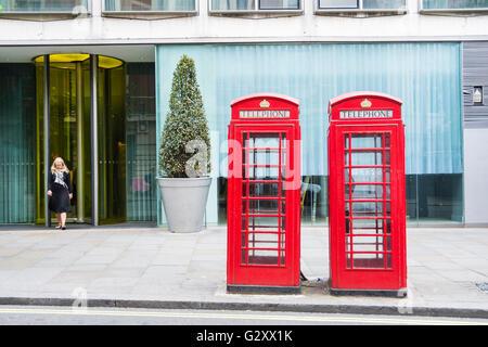 Una mujer emerge de una puerta de oficina detrás de dos kioscos telefónicos de Londres Giles Gilbert Scott K6, de grado II, de color rojo brillante, Londres, Reino Unido