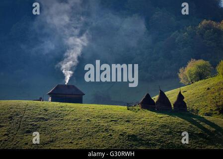 Elevación de humo de la chimenea de una solitaria madera vieja casa cerca de tres montones de heno en una colina de montaña Foto de stock