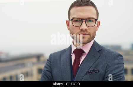 Graves intensos empresario joven con gafas, de pie afuera en un balcón al aire libre mirando a la cámara, la cabeza y el hombro