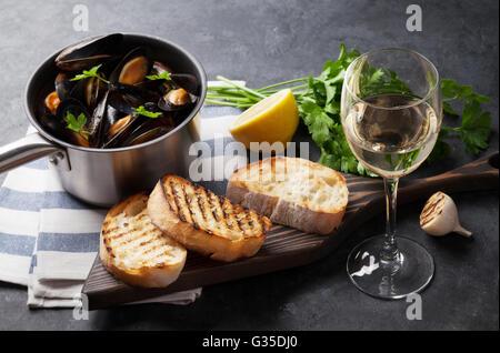 Mejillones en olla de cobre, tostadas de pan y de vino blanco sobre la mesa de piedra. Centrarse en la copa de vino