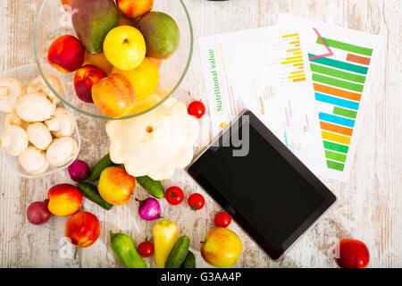 Frutas y vegetales orgánicos sobre la mesa con un tablet PC.