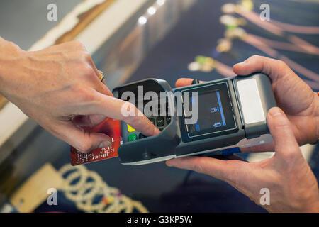Un alto ángulo de vista recortada de womans mano usando la máquina con chip y PIN
