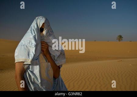 Un hombre local se encuentra en una duna de arena con sedosa tela azul y oro envuelto alrededor de la cabeza y el Foto de stock