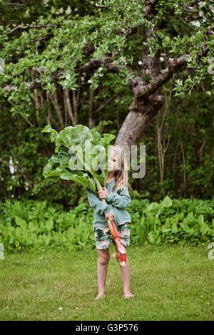 Suecia, Sodermanland, Girl (4-5) de pie sobre el césped y la celebración de grandes hojas de ruibarbo Foto de stock