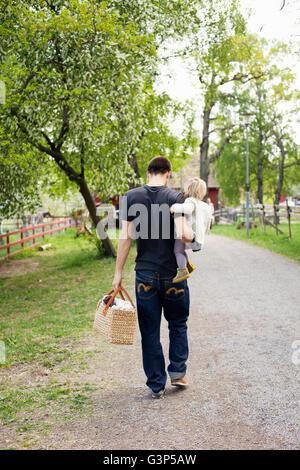 Suecia, Uppland, Padre caminando con su hija (18-23 meses)