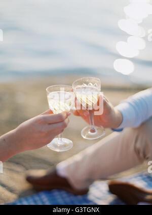 Suecia, Bohuslan, Fjallbacka, Pareja brindando con copas de champán en la playa de arena