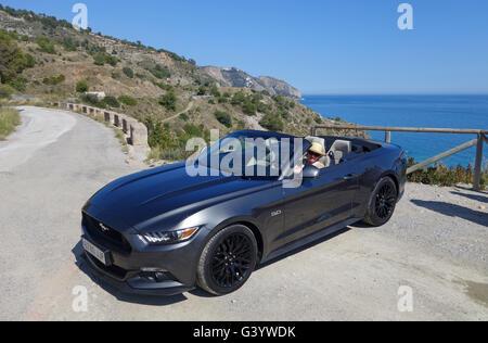 Mujer conduciendo el Ford Mustang convertible de 5 litros V8 con la parte superior abierta.