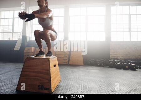 Foto de una mujer joven saltar en una caja como parte de la rutina de ejercicios. Mujer Fitness haciendo crossfit box jump entrenar en el gimnasio.