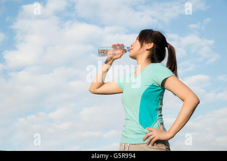 Sport - Mujer joven asiática de agua potable durante la mañana haciendo footing. Mujer Asiática de beber agua de botella.