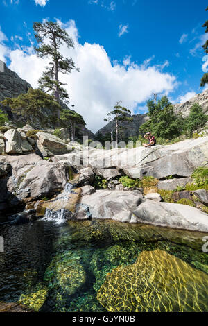 Joven sentado junto a una piscina con una pequeña cascada en las montañas, el río Golo, Parque Natural de Córcega