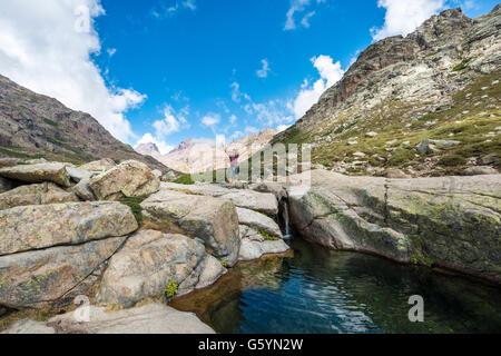 Joven de pie junto a una pequeña cascada con piscina en las montañas, el río Golo, Parque Natural de Córcega