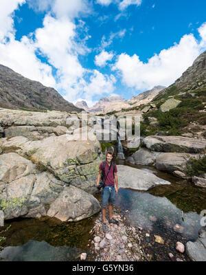 Joven parado en una piscina con una pequeña cascada en las montañas, el río Golo, Parque Natural de Córcega