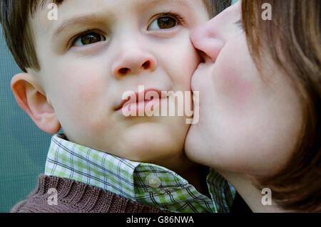Una mujer besando a su hijo. Foto de stock