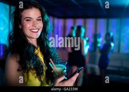 Hermosa mujer con teléfono móvil mientras habiendo cóctel Foto de stock