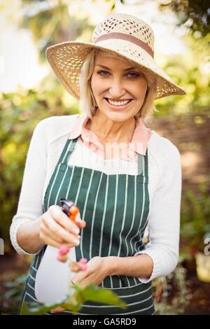 Mujer sonriente mientras que regar las plantas