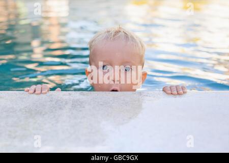 El niño aprende a nadar - cara divertida de Little Baby Boy en la piscina. Activo estilo de vida saludable, deportes de agua, los niños de la actividad física.