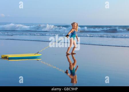 Little Baby Girl - joven surfista con bodyboard tiene diversión en la playa. Estilo de vida familiar, de la gente, el agua la actividad deportiva, surf