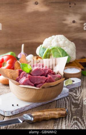 Ternera cruda cortada en trozos con verduras y otros ingredientes listos para cocinar en madera rústica mesa, concepto de cocina ecológica