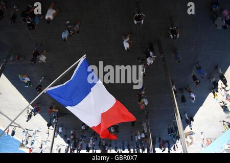 En Marsella, Francia. 07 de julio, 2016. Una bandera francesa vuela por encima de los peatones se reflejan en un Foto de stock