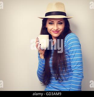 Lindo feliz mujer casual en el sombrero de paja sosteniendo en la mano una taza de té y sonriendo sobre fondo azul.