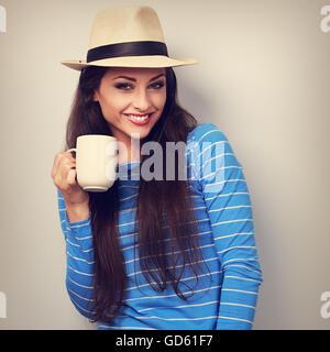 Cute sonriente mujer casual en el sombrero de paja sosteniendo una taza de té y mirando. Tonificado closeup retrato
