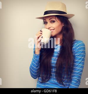 Feliz mujer con sombrero de paja de beber café con divertidas cara emocional. Tonificado closeup retrato