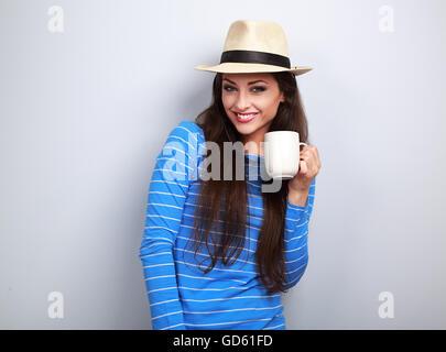 Cute sonriente mujer casual en el sombrero de paja sosteniendo una taza de té y mirando sobre fondo azul.