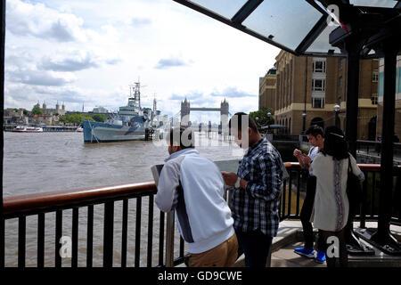 Los turistas en la orilla sur pasarela con HMS Belfast y el Tower Bridge de Londres un hito en el fondo Foto de stock