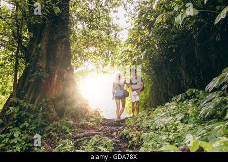 Mujer joven y caminatas en la selva tropical. Par de excursionistas caminando por pista forestal.