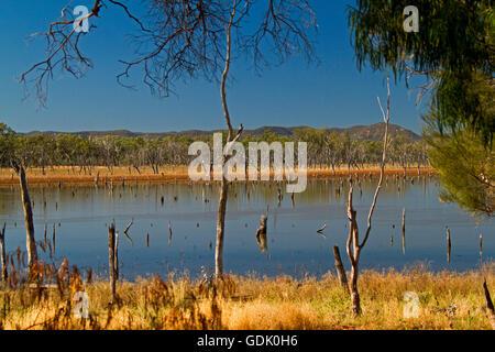 Gran tranquilas aguas azules del lago Nuga Nuga con rangos de Carnarvon resistente en el horizonte bajo un cielo azul en el outback Qld Australia