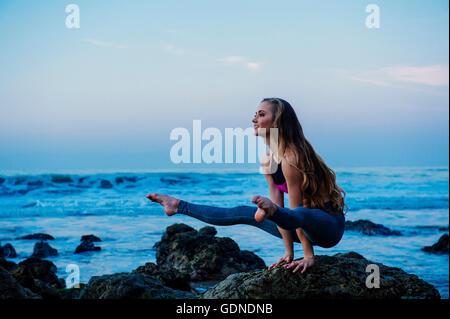 Mujer joven practicando yoga plantean sobre rocas en la playa, Los Ángeles, California, Estados Unidos.