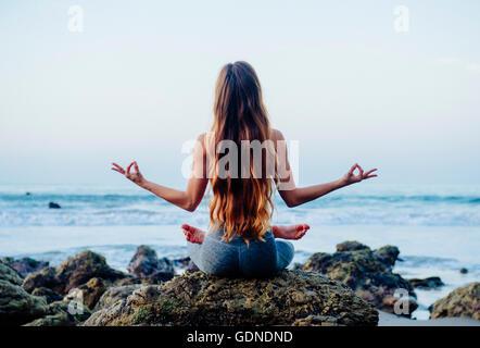 Vista trasera de la mujer joven con pelo largo practicando yoga loto plantean sobre rocas en la playa, Los Ángeles, California, Estados Unidos.