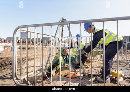 Constructores ayudando a trabajador aprendiz de alcantarilla en construcción