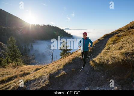 Mujer Trail Running en las montañas por encima de las nubes, Salzburgo, Austria