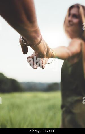 Primer plano del hombre sujetando la mano de su novia en el campo de hierba. POV shot de pareja en la naturaleza.