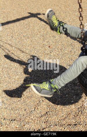 Balanceo de un niño en un columpio de neumático Foto de stock