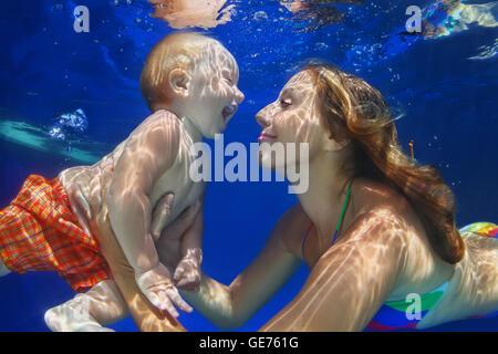 Familia feliz - hijo de la madre, el bebé aprende a nadar y bucear bajo el agua con la diversión en la piscina. Los niños agua ejercicios deportivos.