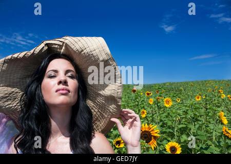 Bastante joven morenita mujer vistiendo gran sombrero en un campo de girasol.