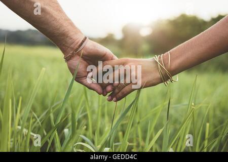 Foto de pareja romántica cogidos de la mano en un campo. Primer plano de un hombre y una mujer con la mano en la mano caminando a través de campo de hierba.