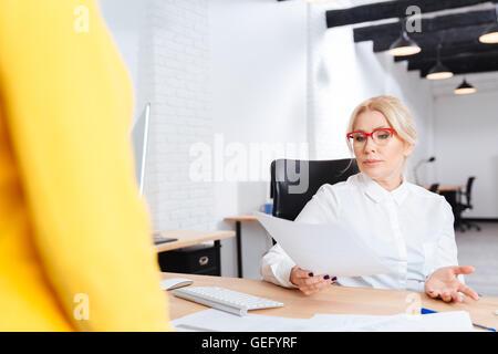 Alegre empresaria maduro hermoso entrevistando candidatos para la nueva posición en la oficina