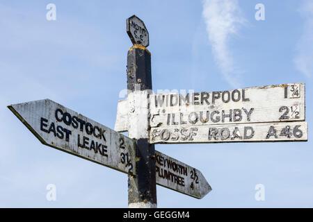 Señal de carretera antiguo de madera que muestra la dirección, el destino y la distancia a los poblados en Nottinghamshire, Inglaterra, Reino Unido.