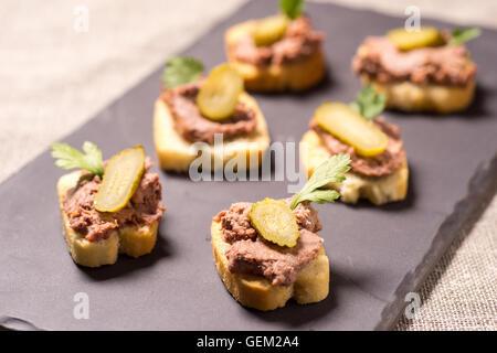 Aperitivo con paté servido sobre una placa de pizarra Foto de stock