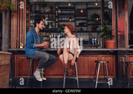 Foto de pareja joven sentado en el cafe contador. El hombre y la mujer joven en la cafetería. Foto de stock