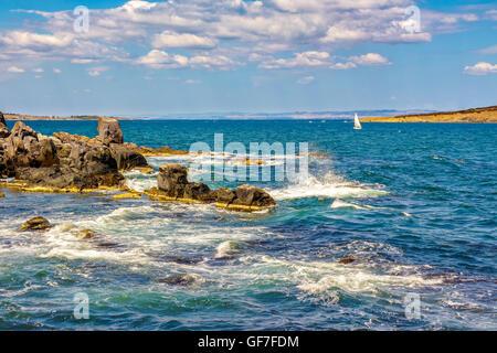 Pequeña embarcación navega a distancia en el mar. Las olas rompen en las enormes rocas en la orilla rocosa en el otro lado del Seascape