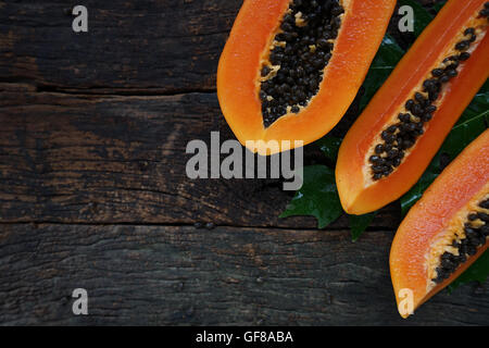Vista superior de la papaya madura con hojas verdes sobre fondo de madera vieja.