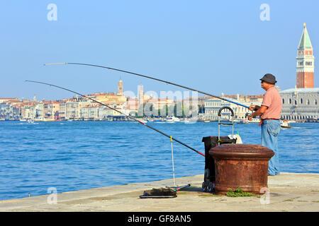 Un pescador pesca con vistas al Palacio Ducal y el Campanile de San Marcos en Venecia, Italia